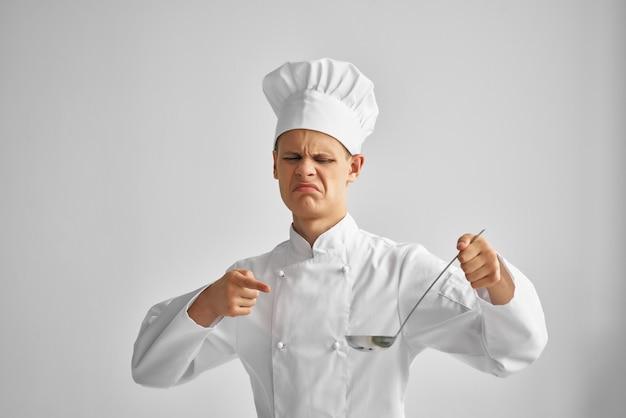 Мужчина-повар в руках пробует блюда профессионального ресторана
