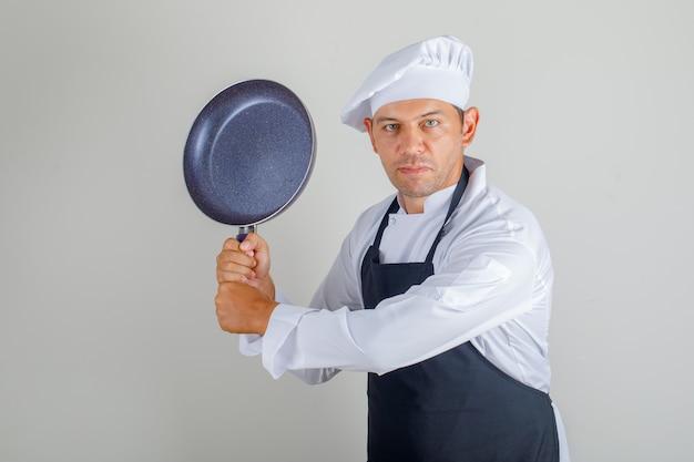 Мужской шеф-повар в шляпе, фартуке и форме держит сковороду, весело проводя время