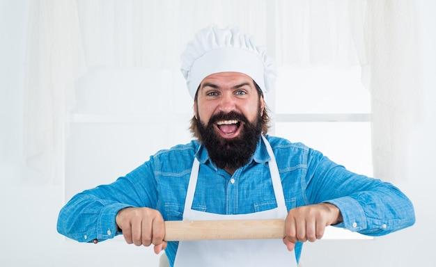 모자를 쓴 남성 요리사가 건강한 식사를 준비합니다. 롤링 핀을 사용하여. 수염과 콧수염 요리 음식을 가진 잘생긴 남자. 전문 레스토랑 요리사 베이킹. 숙련된 제빵사는 요리를 위해 주방 기구를 사용합니다.