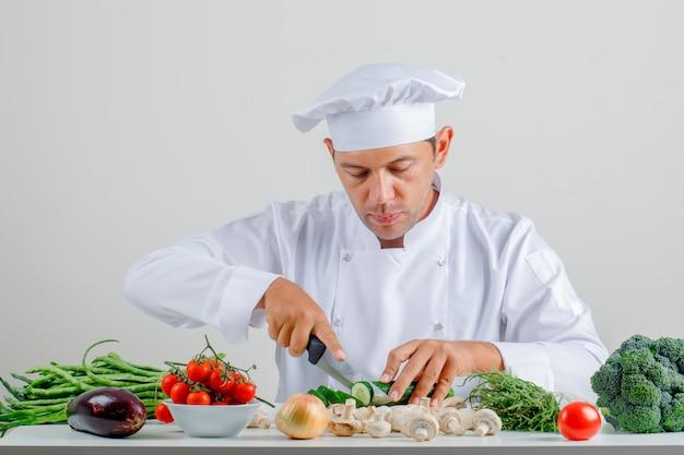 Мужской шеф-повар в форме и шляпе, сидя и резки огурца на кухне