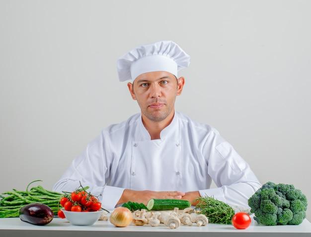 制服を着た男性シェフと帽子が台所に座っています。