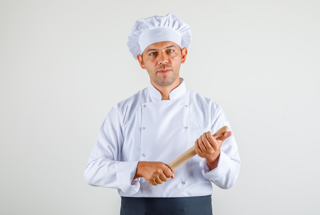 制服、エプロン、帽子、麺棒を押しながら自信を持って男性シェフ