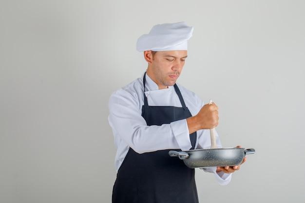 Мужской шеф-повар в форме, фартук и шляпа готовит еду, используя кастрюлю и ложку