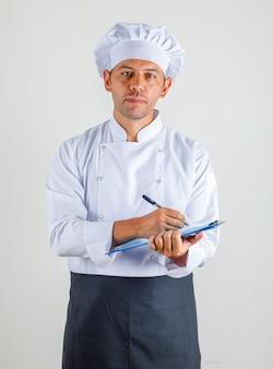 クリップボードにメモを取る制服、エプロン、帽子の男性シェフ