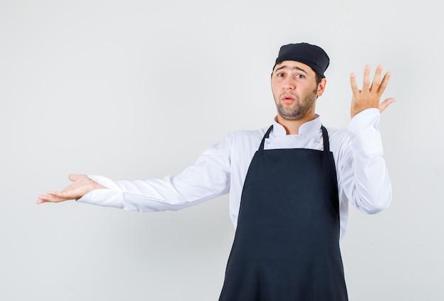 Шеф-повар-мужчина в униформе, в фартуке разводит ладонь, поднимает руку и выглядит смущенным, вид спереди.