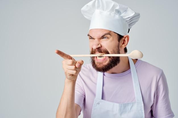 Мужской шеф-повар в единообразной кулинарии кухни ресторана