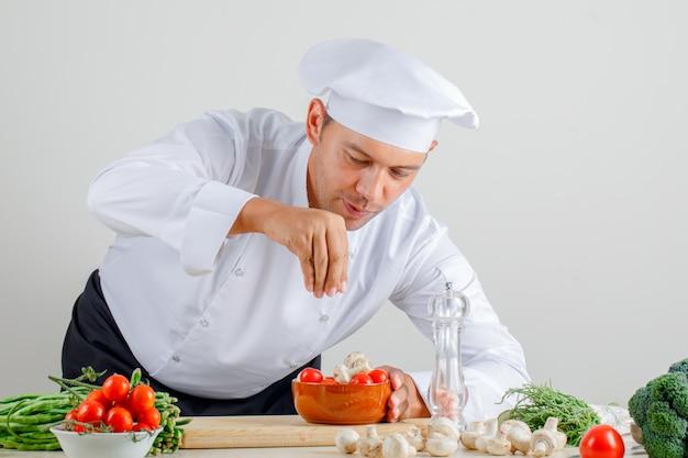 制服を着た男性シェフ、帽子、エプロンがキッチンの食べ物にスパイスを追加
