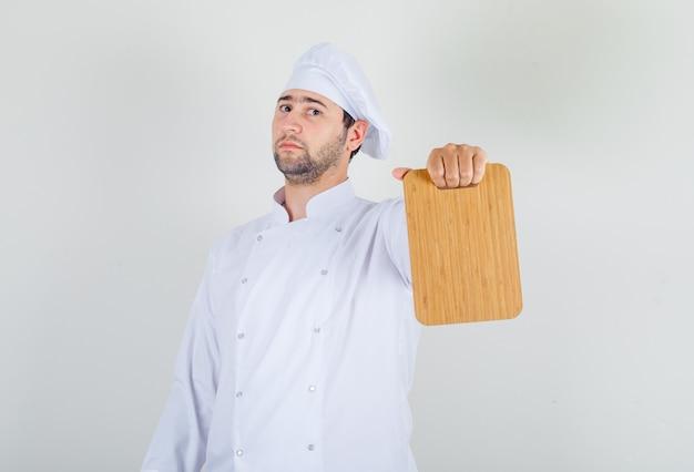 Шеф-повар-мужчина в белой форме держит разделочную доску и выглядит уверенно