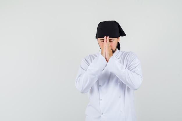 흰색 제복을 입은 남성 요리사가 손을 잡고 기도하는 몸짓과 희망적인 앞모습을 보고 있습니다.