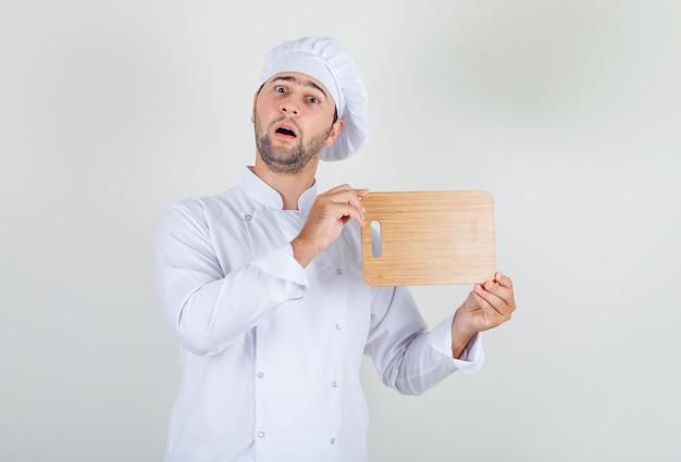 나무 커팅 보드를 들고 놀란 흰색 제복을 입은 남성 요리사