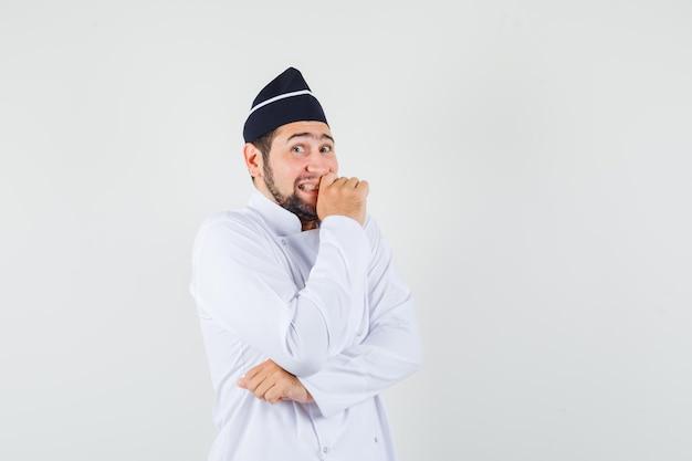 흰색 제복을 입은 남성 요리사는 웃고 있는 동안 행복하고 앞모습을 보고 있습니다.