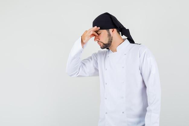 흰색 제복을 입은 남성 요리사가 눈과 코를 문지르고 피곤해 보이는 전면 전망.