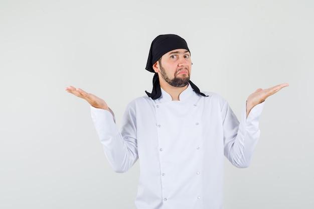 Мужчина-шеф-повар в белой форме показывает беспомощный жест и выглядит смущенным, вид спереди.