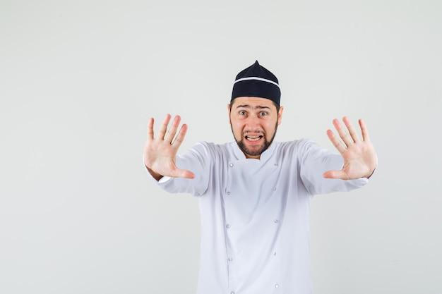 Шеф-повар-мужчина в белой форме показывает жест стоп и выглядит испуганным, вид спереди.