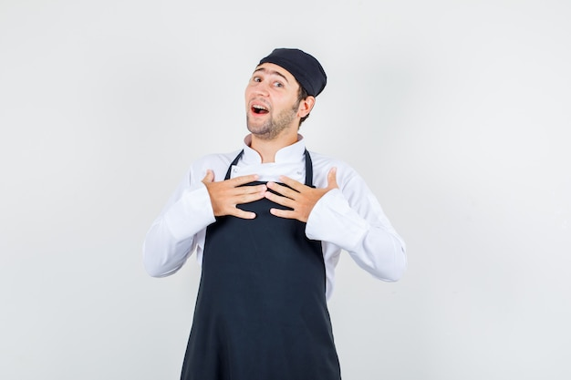 制服、エプロンで胸に手を当てて喜んでいる男性シェフ。正面図。