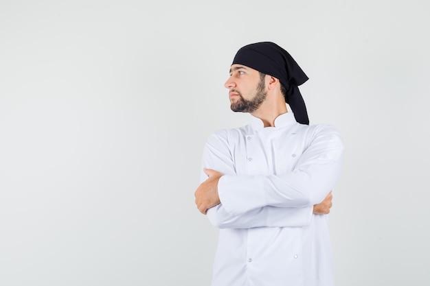 白い制服を着た腕を組んで脇を見て、焦点を合わせた、正面図を探している男性シェフ。