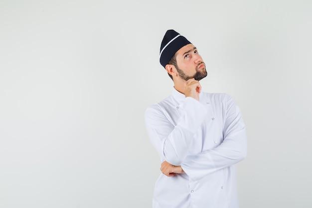 Шеф-повар-мужчина, глядя вверх в белой форме и задумчиво, вид спереди. место для текста
