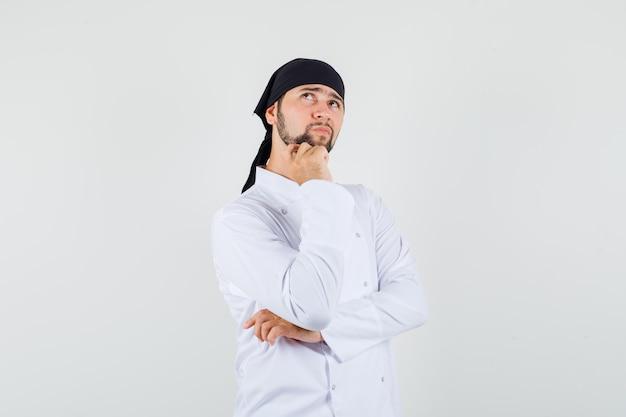 Шеф-повар-мужчина, глядя вверх в белой форме и задумчиво, вид спереди.
