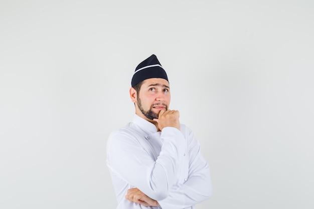 Chef maschio alzando lo sguardo con la mano sul mento in uniforme bianca e guardando pensieroso. vista frontale.