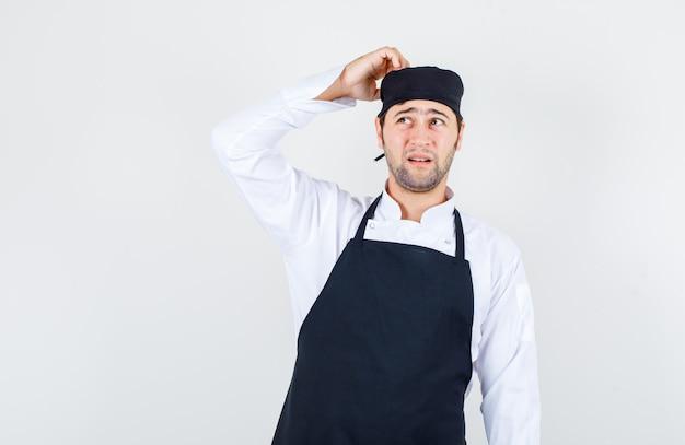 Cuoco unico maschio che osserva in su con la mano sulla testa in uniforme, grembiule e guardando pensieroso, vista frontale.