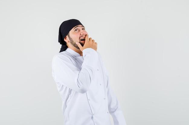 Cuoco unico maschio che cerca con la mano sulla bocca in uniforme bianca e sembra allegro. vista frontale.