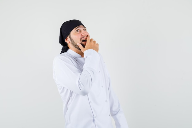 白い制服を着て口に手を当てて見上げる男性シェフが元気そうに見えます。正面図。