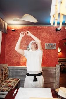 男性シェフがキッチンで生地を作ります。自家製のリンゴのシュトルーデル料理、甘いデザートの準備