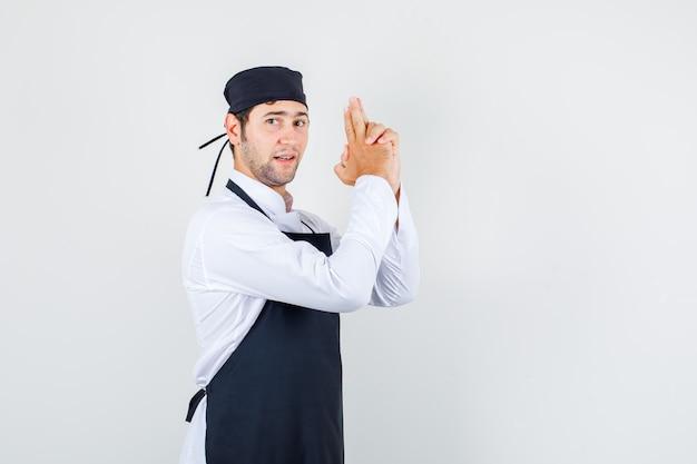 Мужской шеф-повар делает жест стрельбы из пистолета в униформе, фартуке и выглядит уверенно, вид спереди.