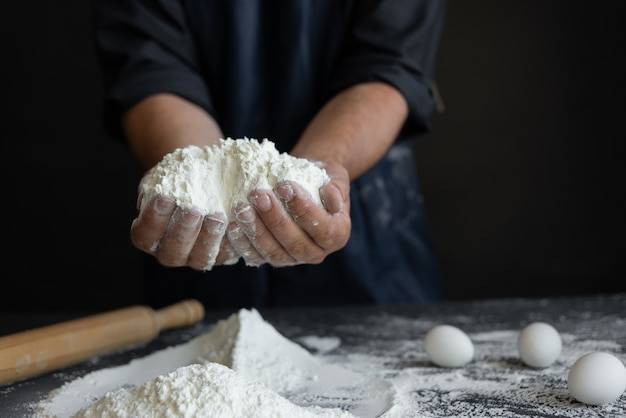 男性シェフ、男性の手は黒いテーブルの上に大きな一握りの小麦粉を持っています。ベーカリーのコンセプト