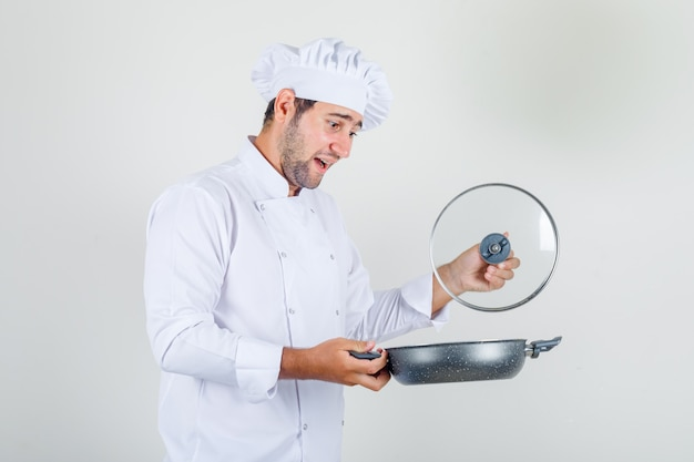 Male chef opening lid of pan in white uniform and looking cheerful.