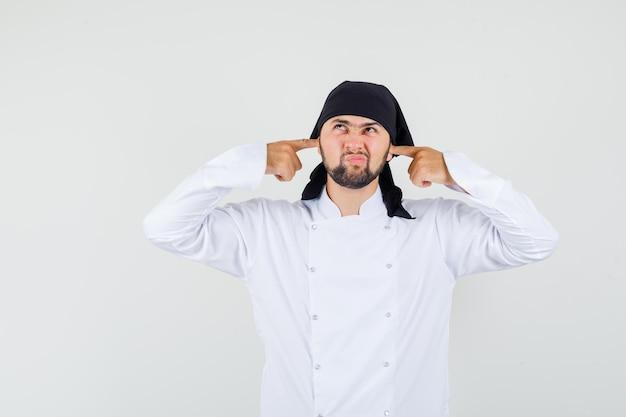 Cuoco unico maschio che tappa le orecchie con le dita in uniforme bianca e sembra annoiato. vista frontale.
