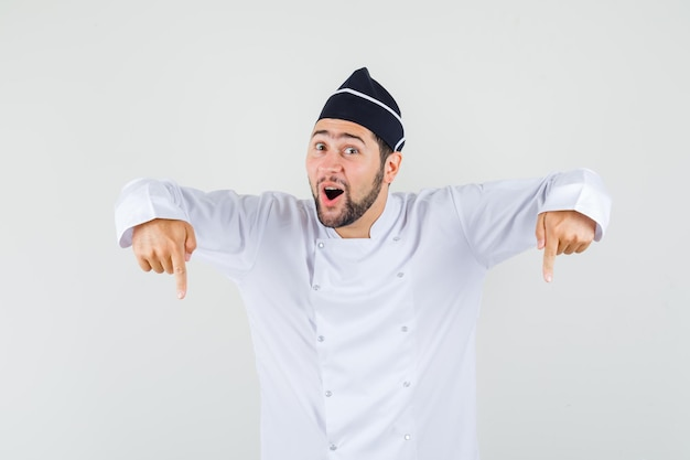 Male chef pointing down in white uniform and looking curious. front view.