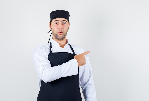 Male chef pointing finger to side in uniform, apron and looking surprised. front view.