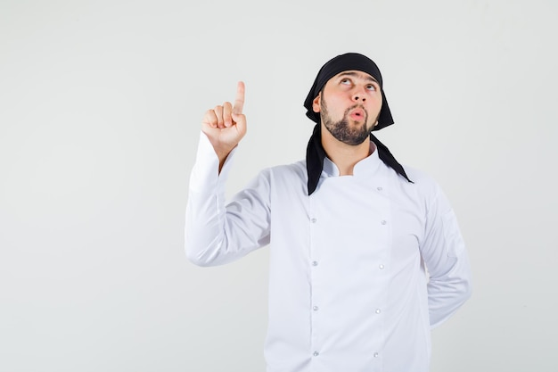 白い制服を着て指を上に向け、焦点を合わせた男性シェフ、正面図。
