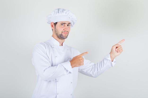 Chef maschio che punta le dita lontano in uniforme bianca e sembra positivo