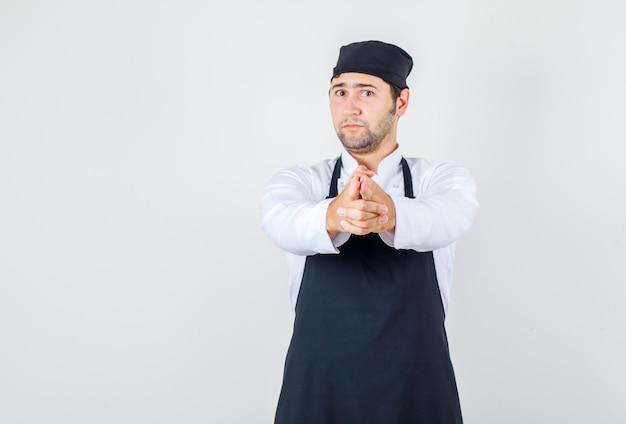Chef maschio che indica il gesto della pistola in uniforme, grembiule, vista frontale.