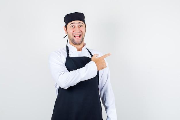 Chef maschio che punta a lato in uniforme, grembiule e guardando allegro, vista frontale.
