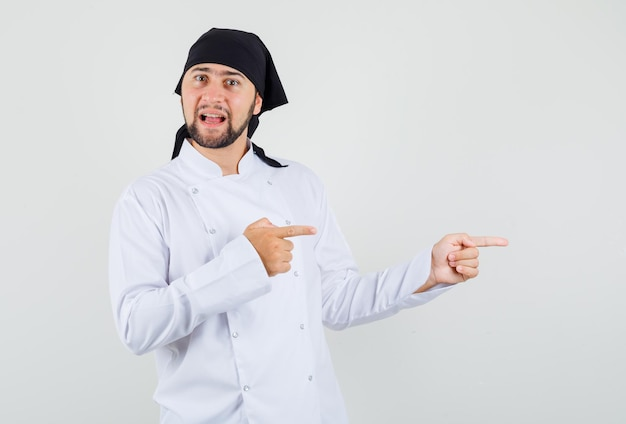 Male chef pointing to the side in white uniform and looking confident. front view.