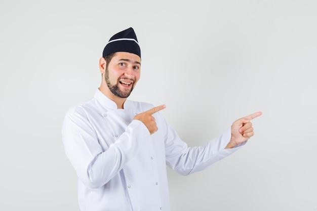 Cuoco unico maschio che indica il lato in uniforme bianca e sembra allegro, vista frontale.