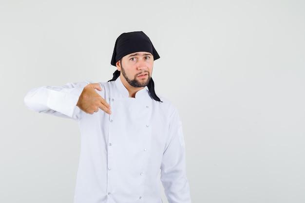 白い制服を着た男性シェフが2本の指を自分に向けて困惑している。正面図。