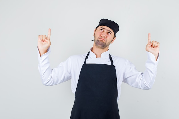 Male chef pointing up fingers in uniform, apron and looking gloomy , front view.
