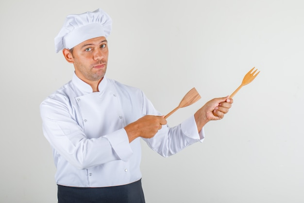 Male chef pointing wooden kitchen utensils away in uniform, apron and hat