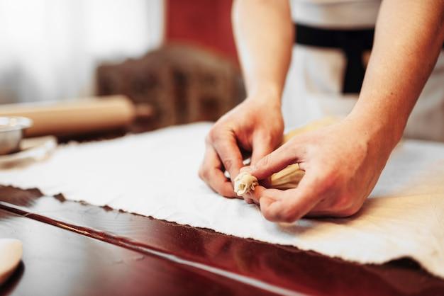 男性シェフは、アップルシュトルーデル、ベーカリー料理を準備します。自家製の甘いデザート、準備プロセス
