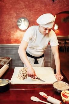 男性シェフが木製キッチンテーブルにリンゴのシュトルーデルを準備します。自家製の甘いデザート、パイの準備プロセス