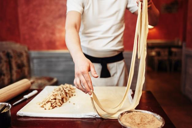 男性シェフが木製キッチンテーブル、ペストリーの準備プロセスでアップルシュトルーデルの生地を準備します。自家製の甘いデザート