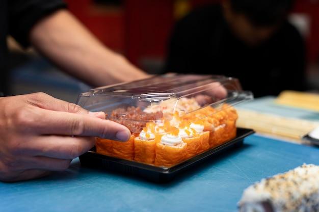 Шеф-повар-мужчина готовит заказ суши на вынос
