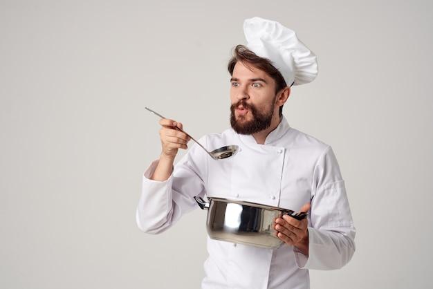 Шеф-повар-мужчина готовит еду в профессиональной кухне кастрюли