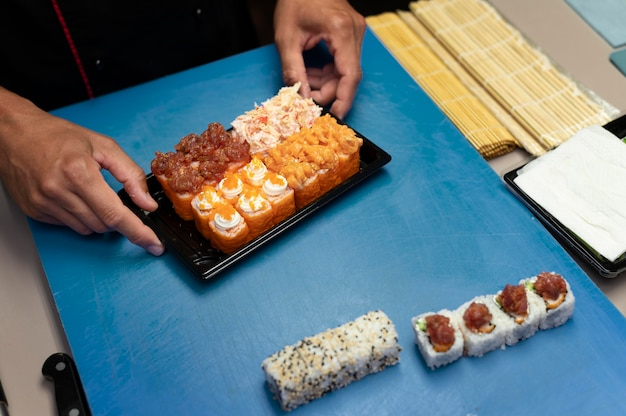 Male chef preparing a sushi order for a takeaway