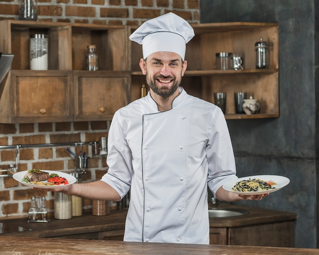Male chef presenting delicious dishes in the kitchen