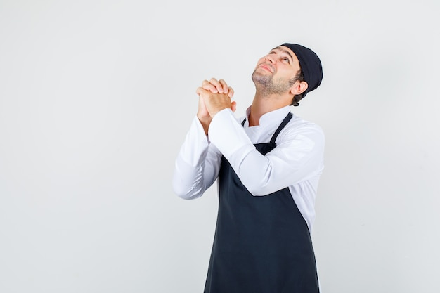 Chef maschio predando con le mani giunte in uniforme, grembiule e guardando speranzoso, vista frontale.
